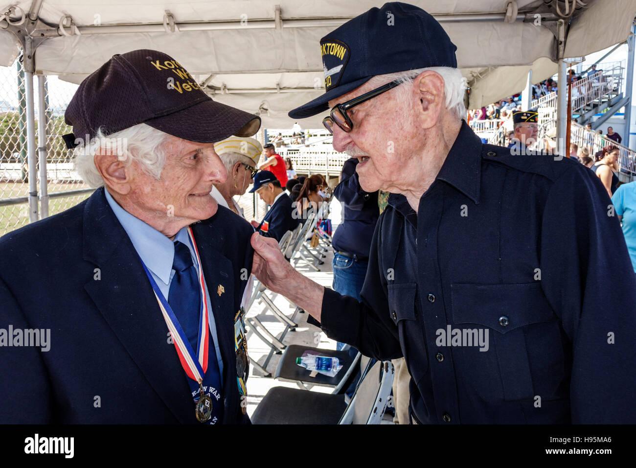Miami Florida Beach Veterans Day celebration activities Korean War Veteran senior friends talking reminiscing - Stock Image