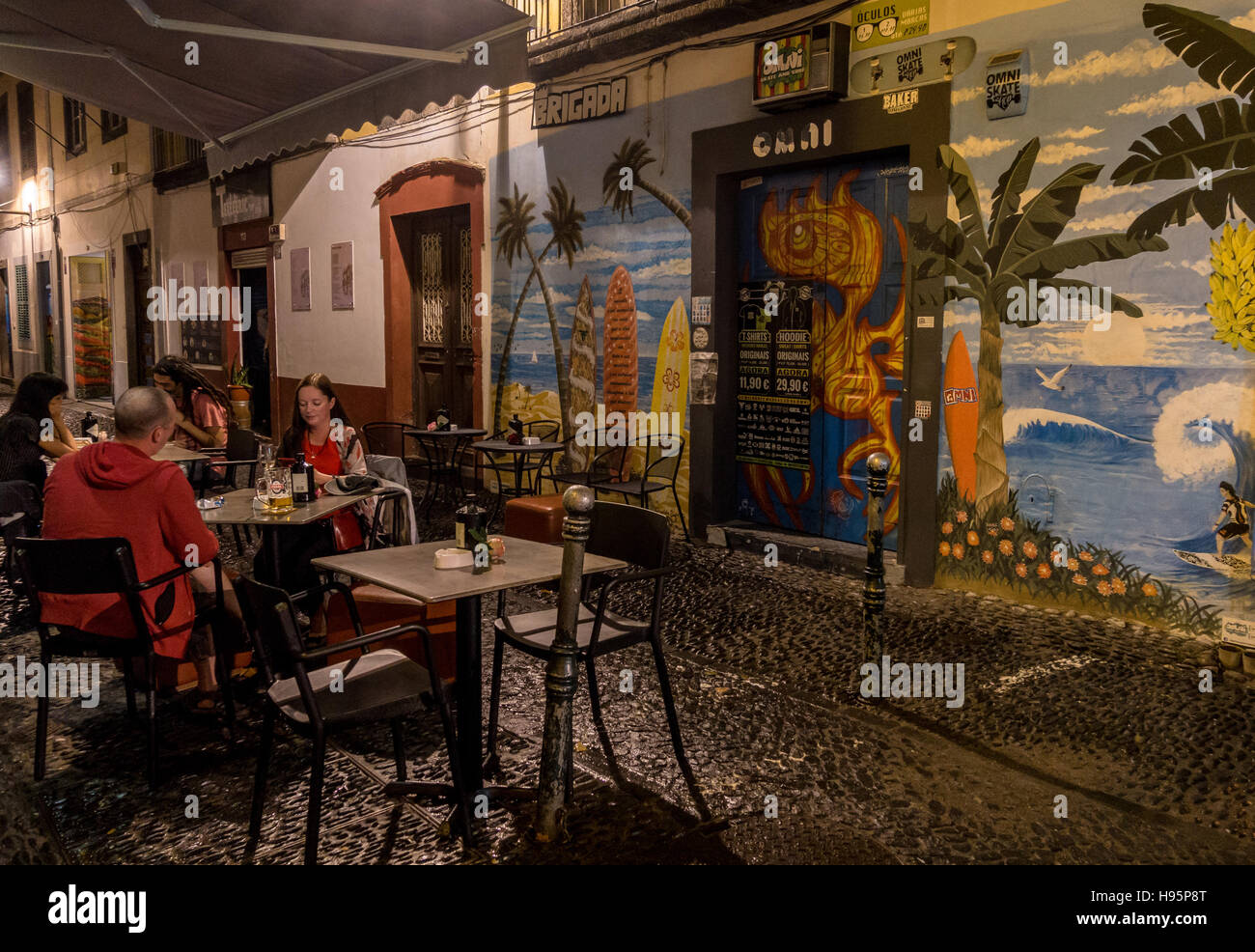 Diners outside a restaurant in an old street at night with murals on the walls - Stock Image