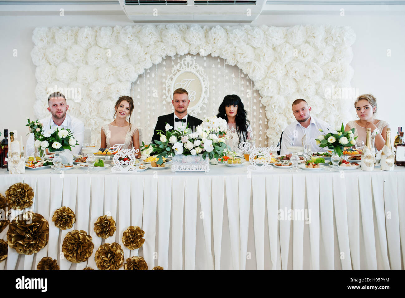 Wedding Couple With Best Man And Bridesmaid Sitting On