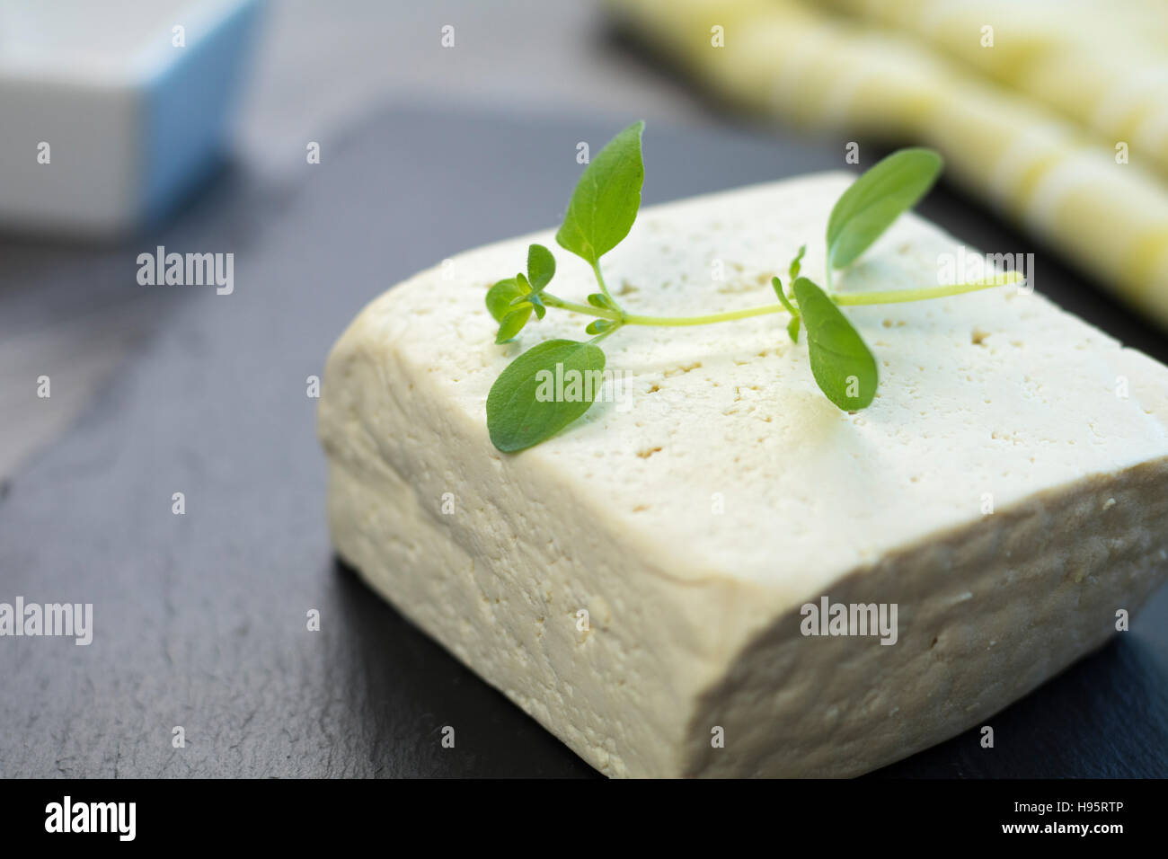 Big tofu chunk on a black stone tray with fresh oregano and green cloth in the background. - Stock Image