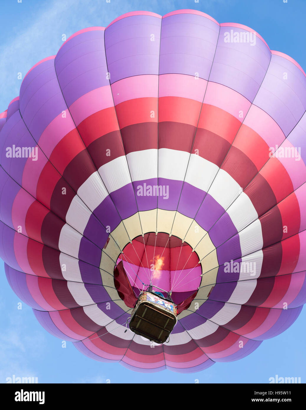Hot air balloon gas flame is visible as it rises during mass ascension at Albuquerque International Balloon Fiesta, New Mexico Stock Photo