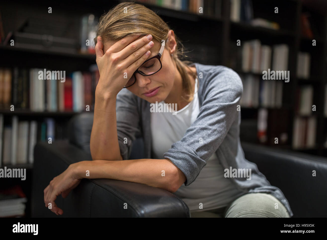 Woman suffering from depression Sitting in a chair (shallow DOF) - Stock Image