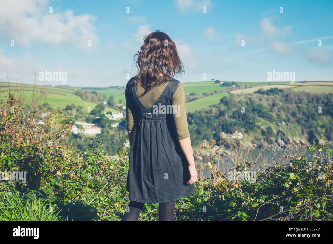 A young woman is standing on a hilltop and is admiring the countryside - Stock Image