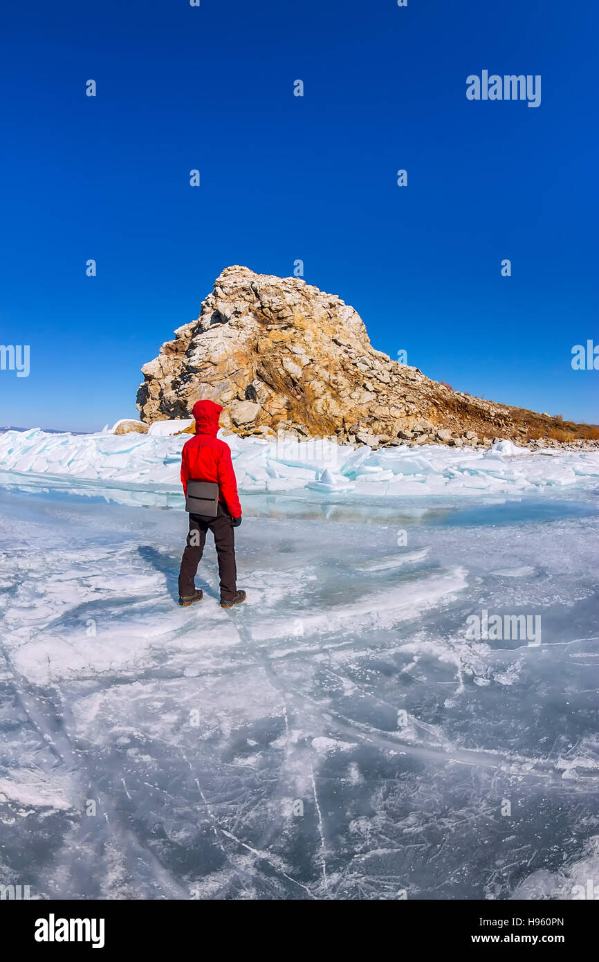 Man tourist is standing at the rock cores on the blue ice of Lake Baikal. - Stock Image