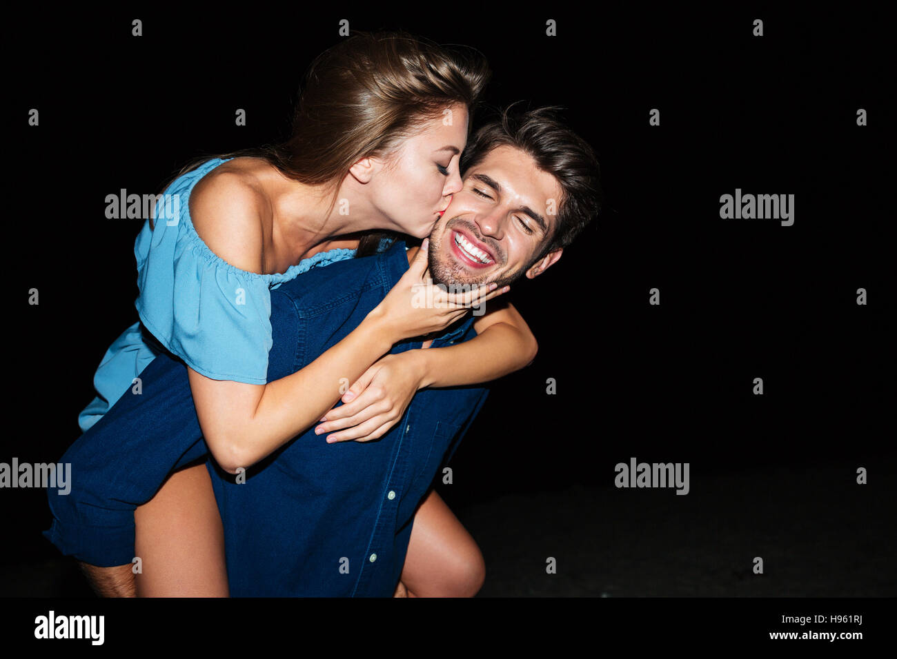 Happy young couple kissing and having fun on the beach at night - Stock Image