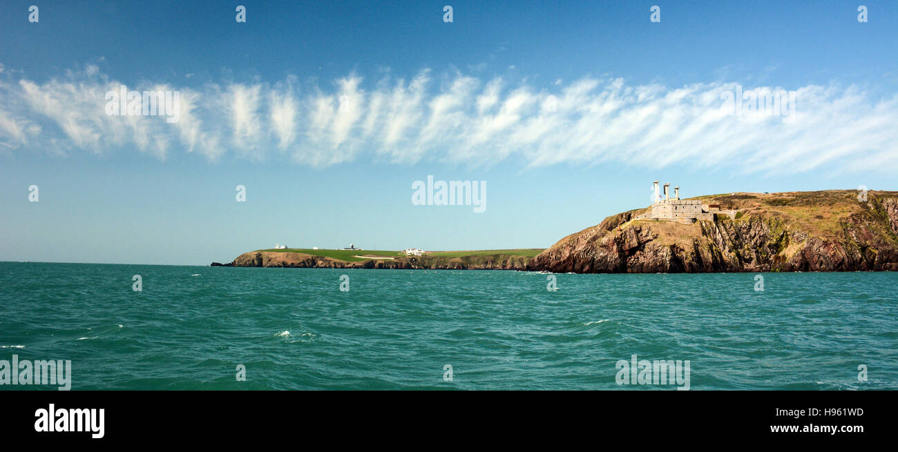 Band of fair weather cirrus clouds over St Ann's Head and lighthouse in the distance off Dale in Pembrokeshire - Stock Image