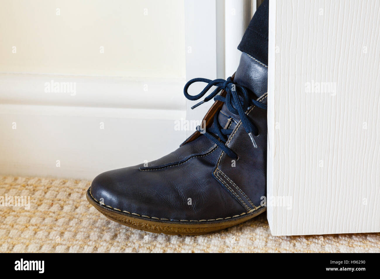 An unwelcome person getting a foot in the open door gap inside a house. England, UK, Britain - Stock Image