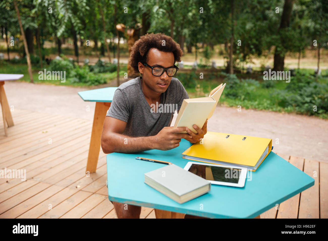 Concentrated african young man sitting and reading book outdoors - Stock Image