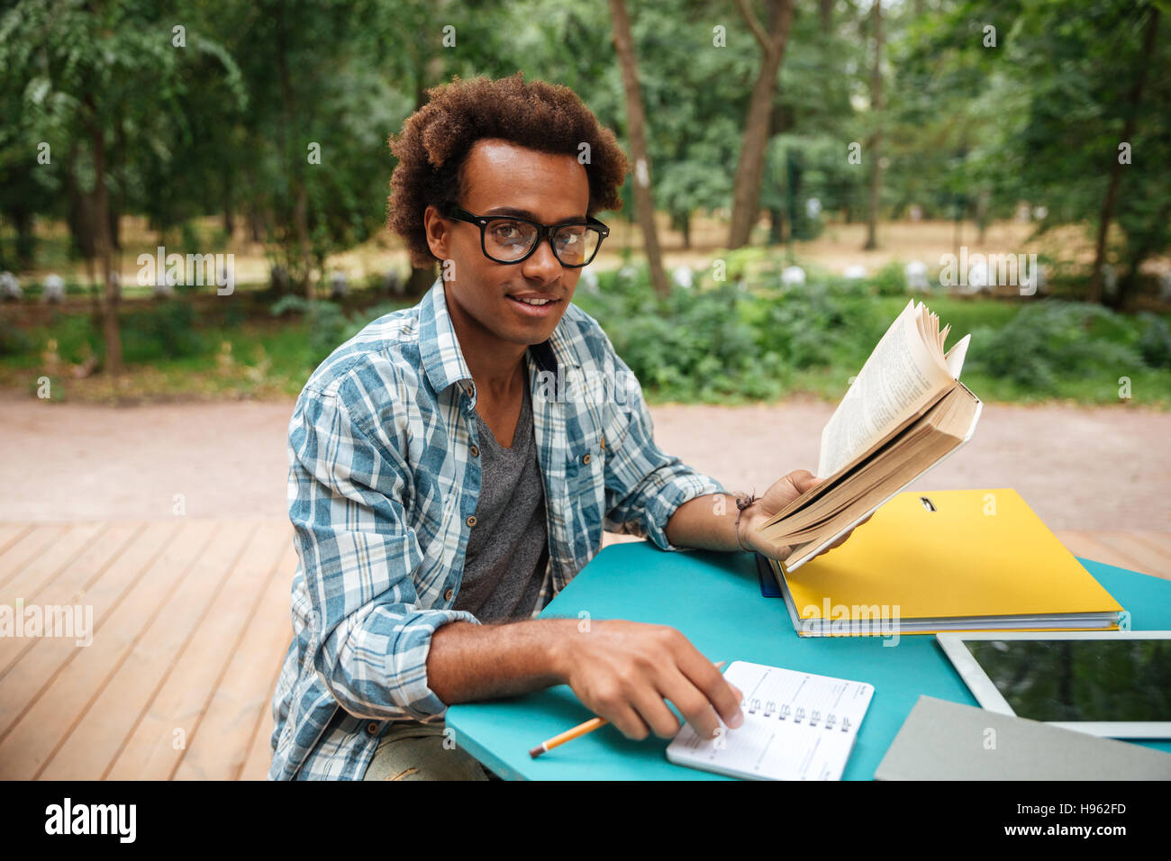 Happy attractive african young man studying outdoors - Stock Image