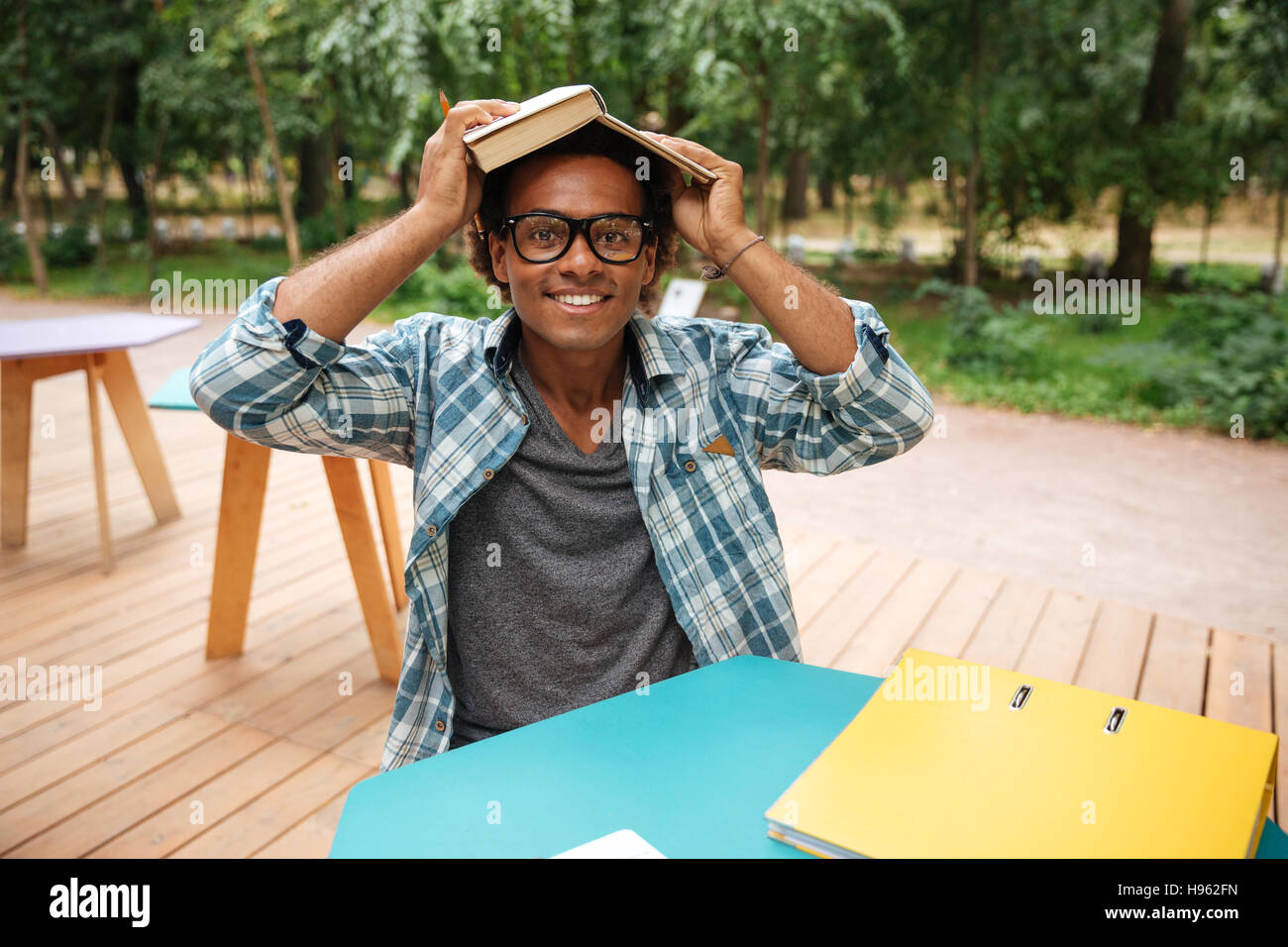 452aba32ad45 Happy african young man in glasses studying and having fun in outdoor cafe  - Stock Image