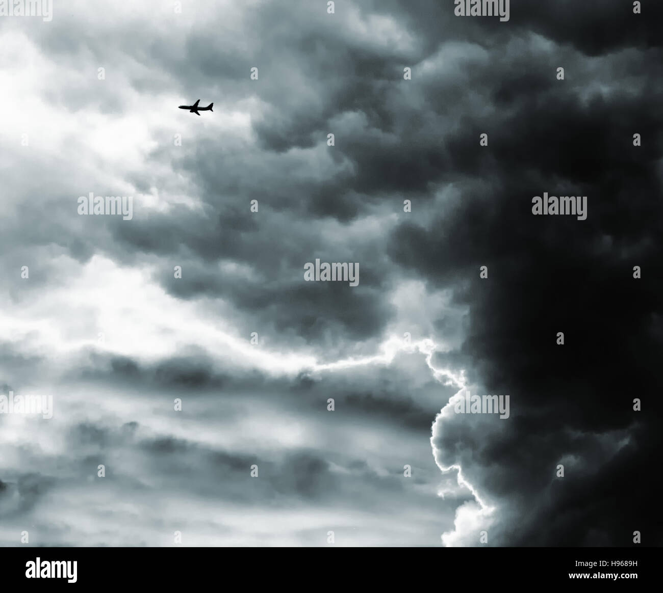 A distant aircraft flying past a dramatic, towering, dark storm cloud - Stock Image