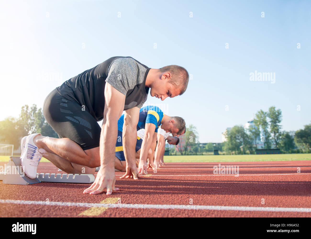 Close-up side view of cropped people ready to race on track field - Stock Image