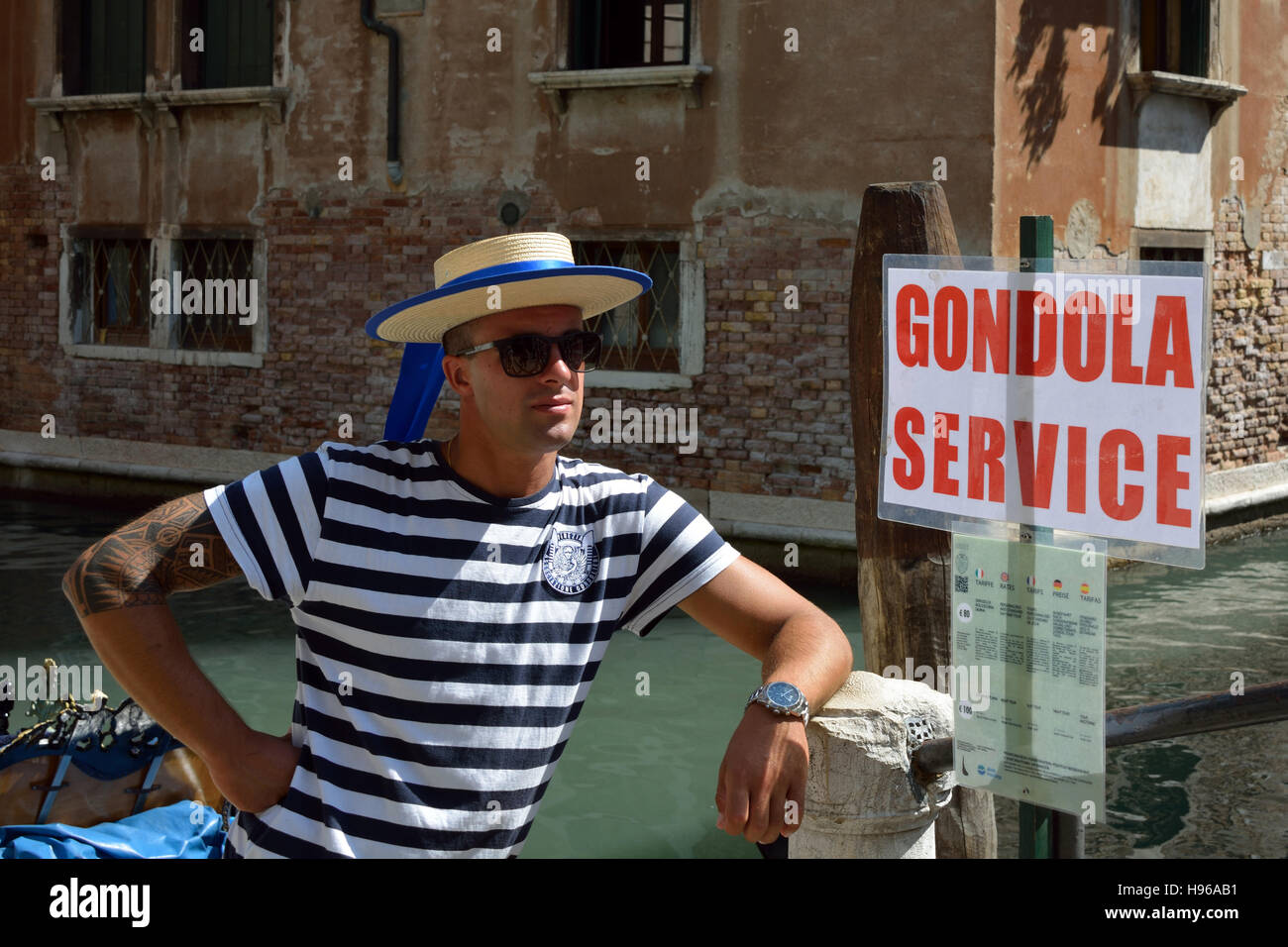 Gondolier with the typical headgear on a canal of Venice in Italy. - Stock Image