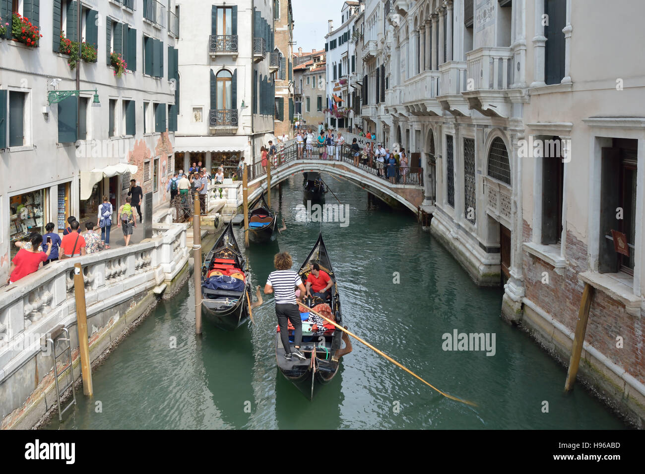 Gondolier with Tourists on a canal in Venice. - Stock Image