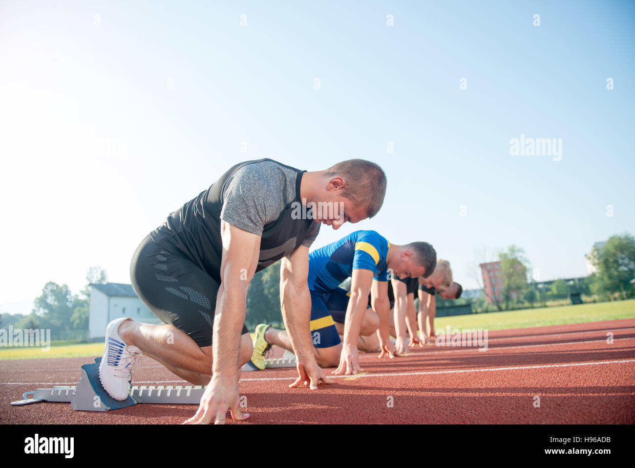 Close-up side view of cropped people ready to race on track field Stock Photo