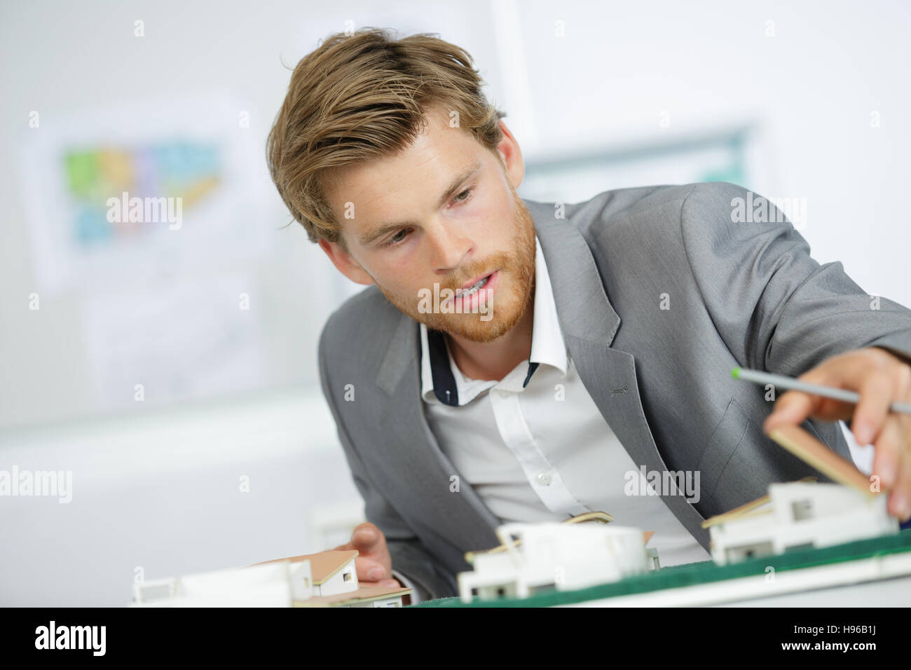 handsome architect working on house models - Stock Image