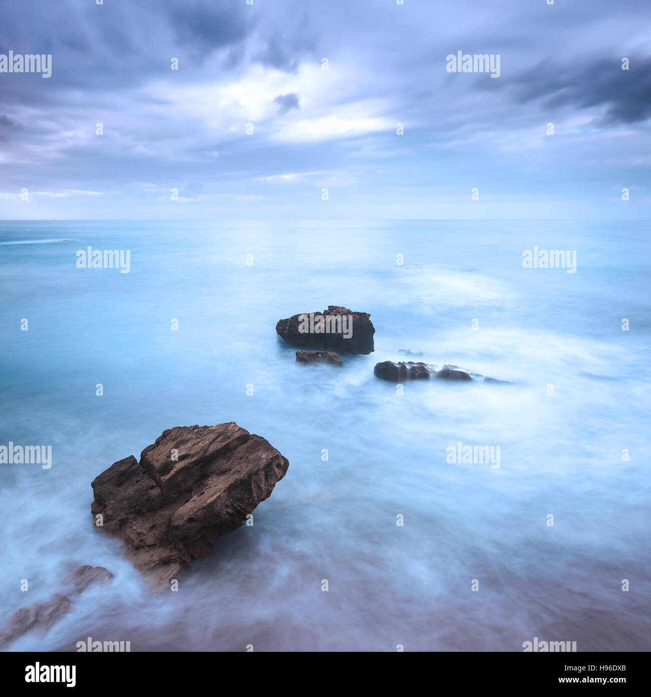 Rocks in a blue ocean waves under cloudy sky in a bad weather. Long exposure photography Stock Photo