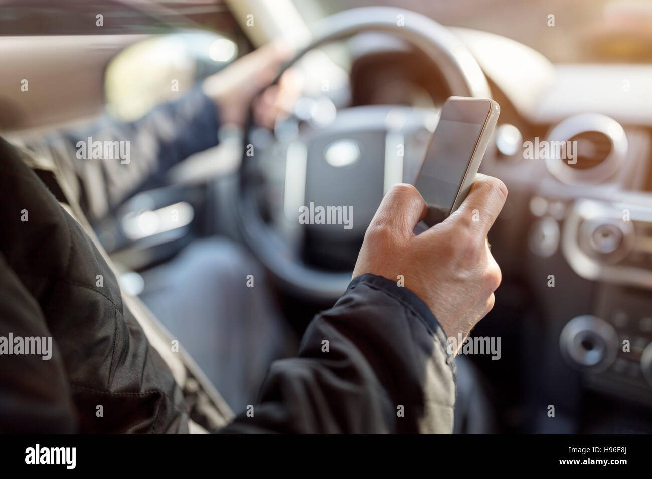 Texting while driving using cell phone in car - Stock Image