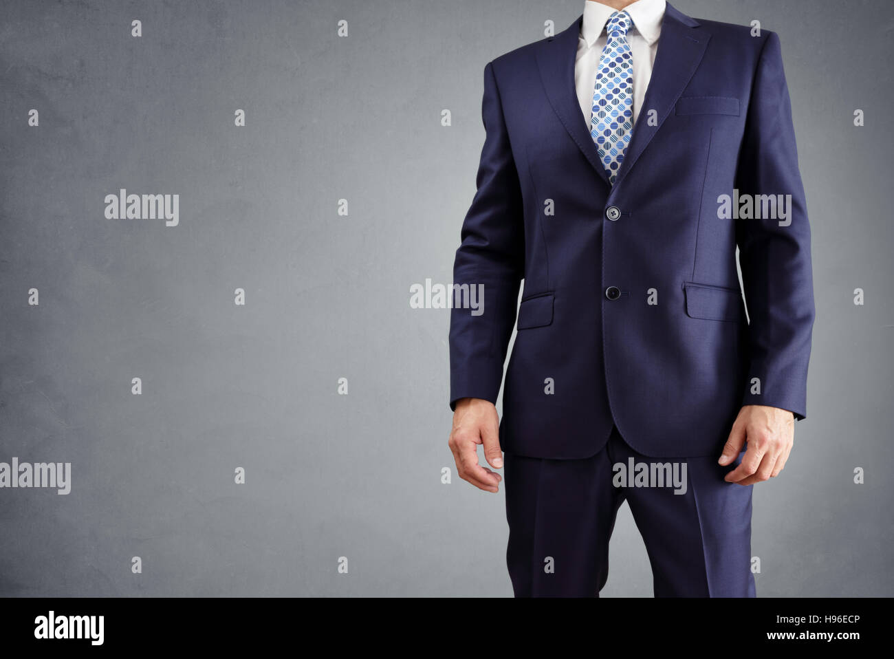 Businessman in a suit isolated on gray background - Stock Image
