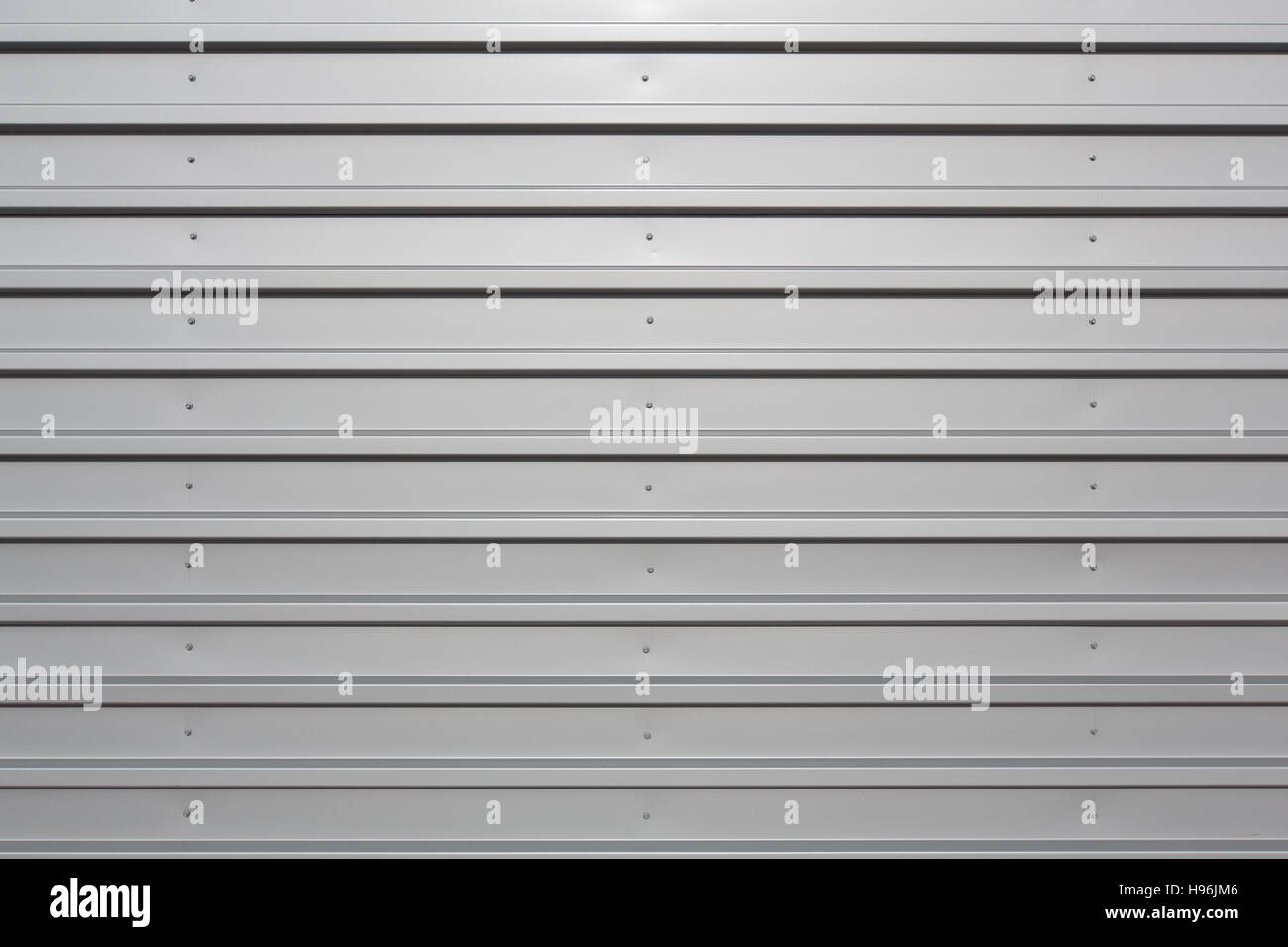 Silver corrugated metal with bolts, horizontal orientation - Stock Image