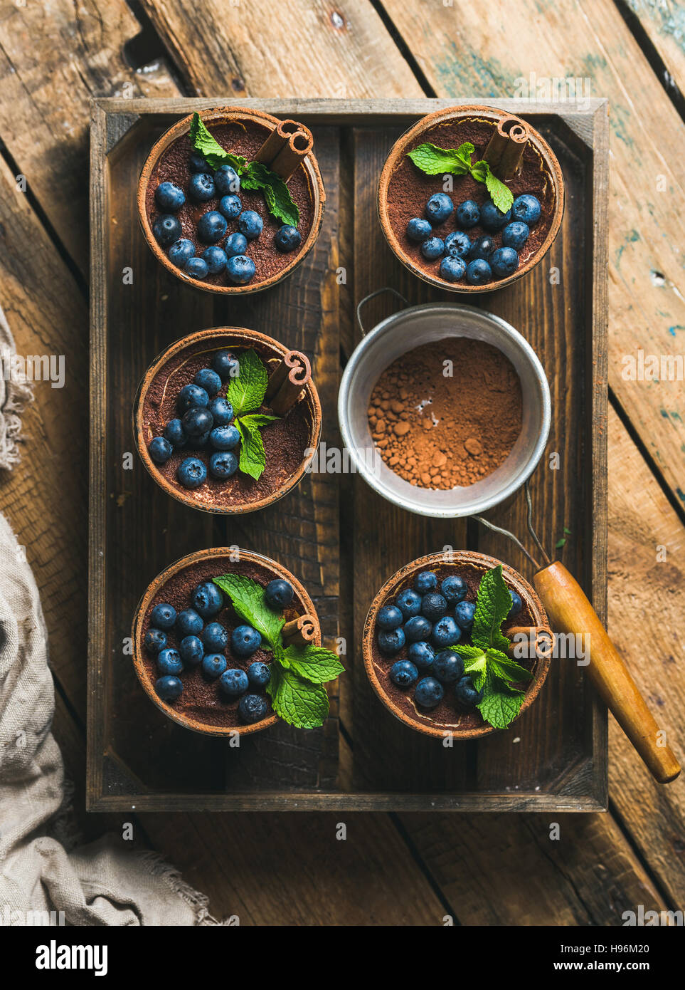 Homemade Tiramisu and sieve with cocoa powder in wooden tray - Stock Image