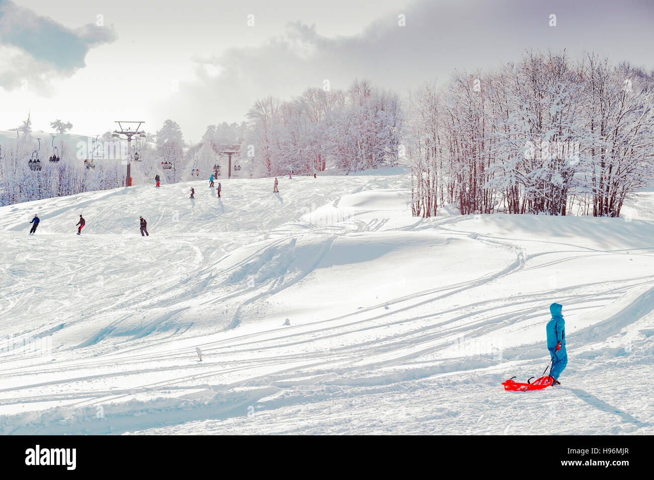 Skiers skiing in a track on ski resort at winter - Stock Image
