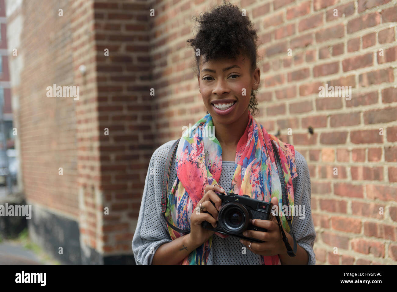 Young woman with digital camera against brick wall - Stock Image