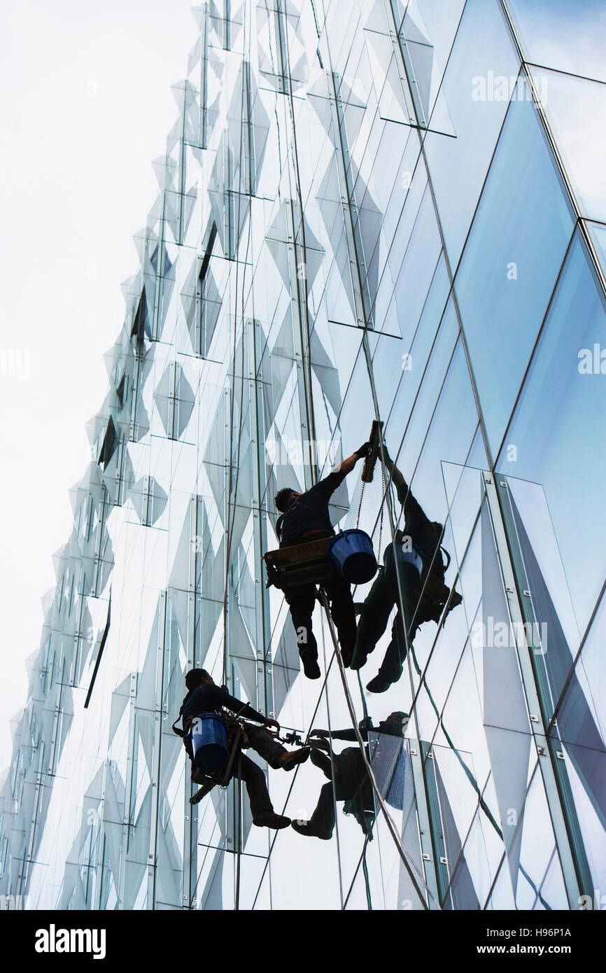 USA, New York, New York City, Windows washers cleaning glass facade of office building - Stock Image