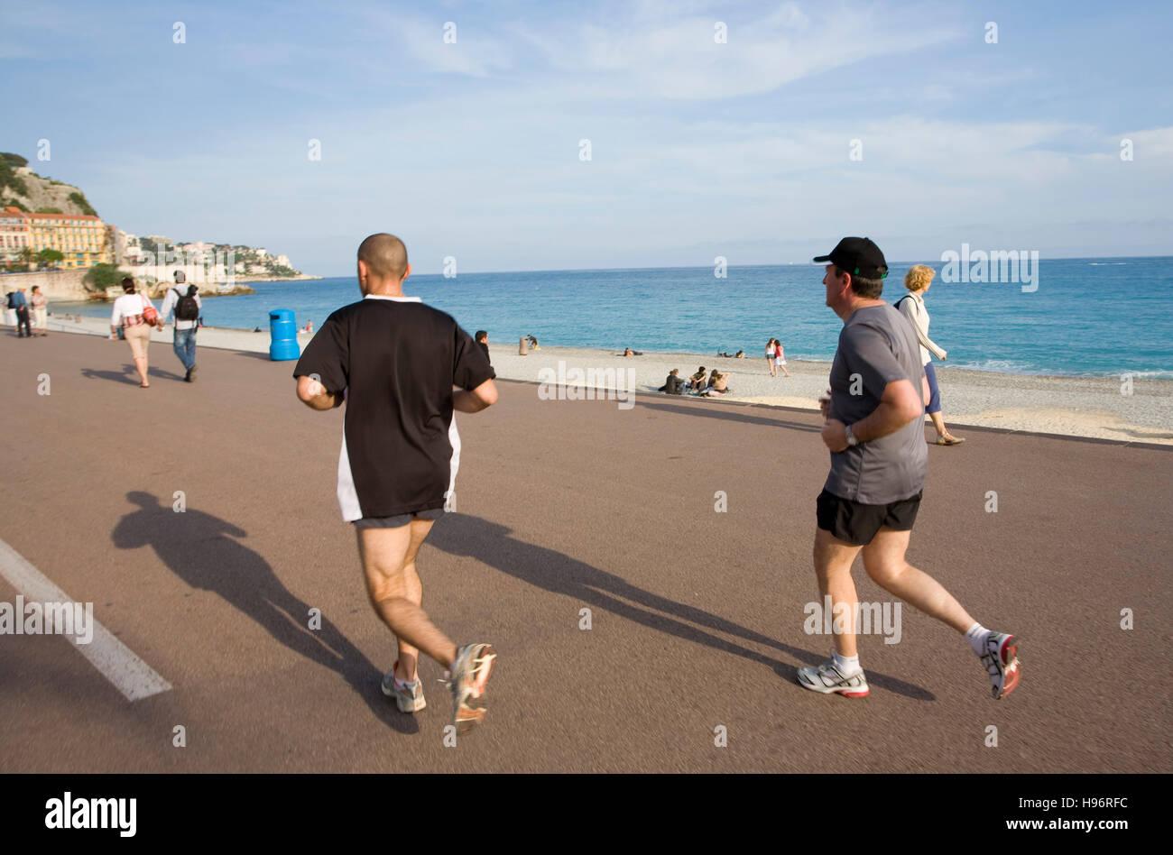 Men jogging on Promenade des Anglais, beach, Nice, Cote d'Azur, France - Stock Image