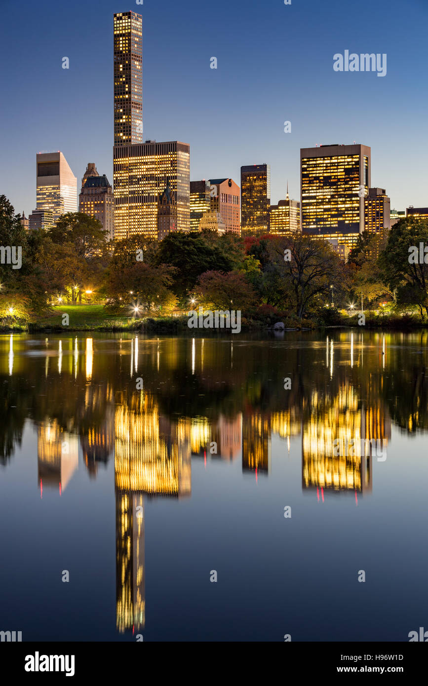 The Lake in Central Park at twilight with New York City lights and Manhattan Midtown skyscrapers reflecting into - Stock Image