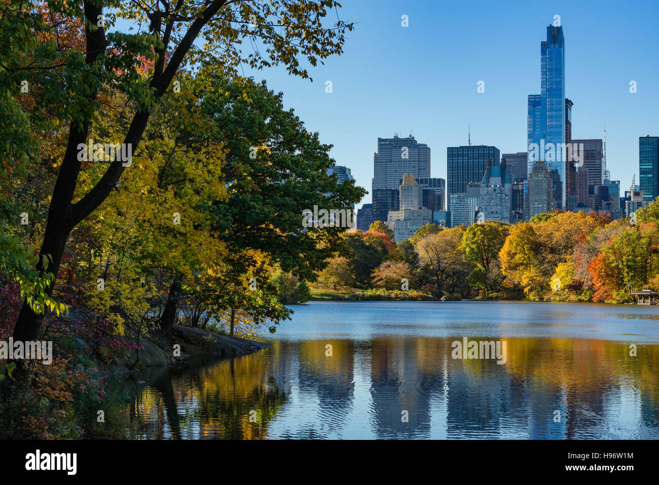 Autumn in Central Park at The Lake with Midtown skyscrapers. Cityscape sunrise view, Manhattan, New York City - Stock Image