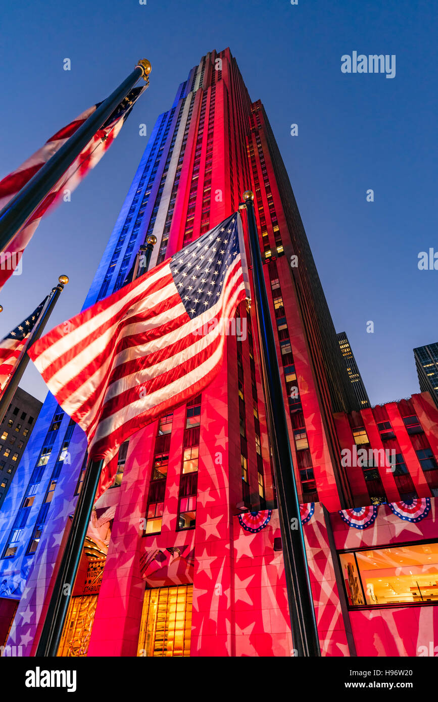 Rockefeller Center at twilight illuminated in white, red and blue. American flags flap in the wind. Midtown Manhattan, - Stock Image