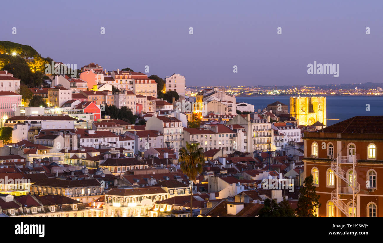 Cityscape of Lisbon, Portugal, seen from Miradouro Sao Pedro de Alcantara at night - Stock Image