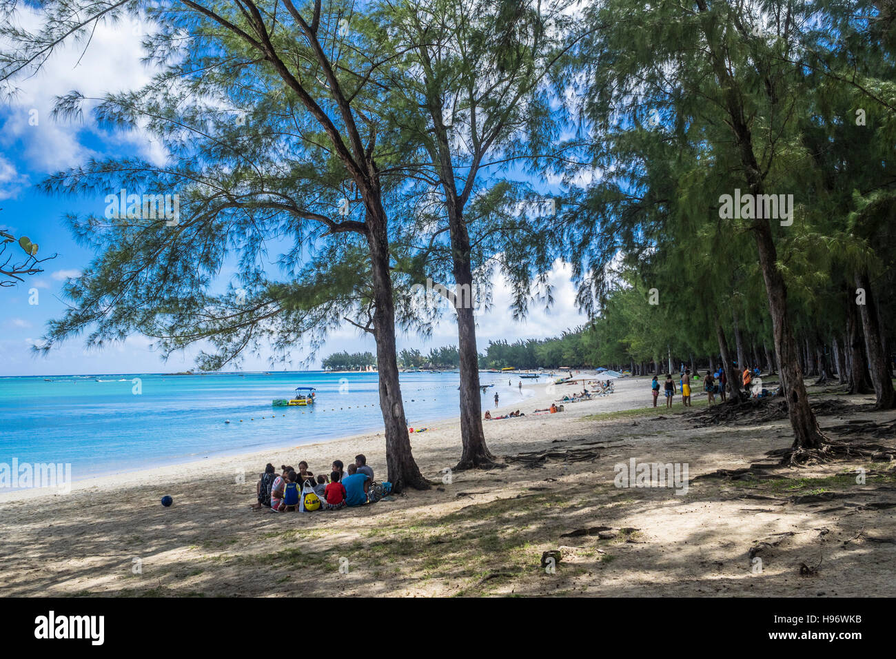 Family picnicking in shade on beach, Mon Choisy, Mauritius, Indian Ocean Stock Photo