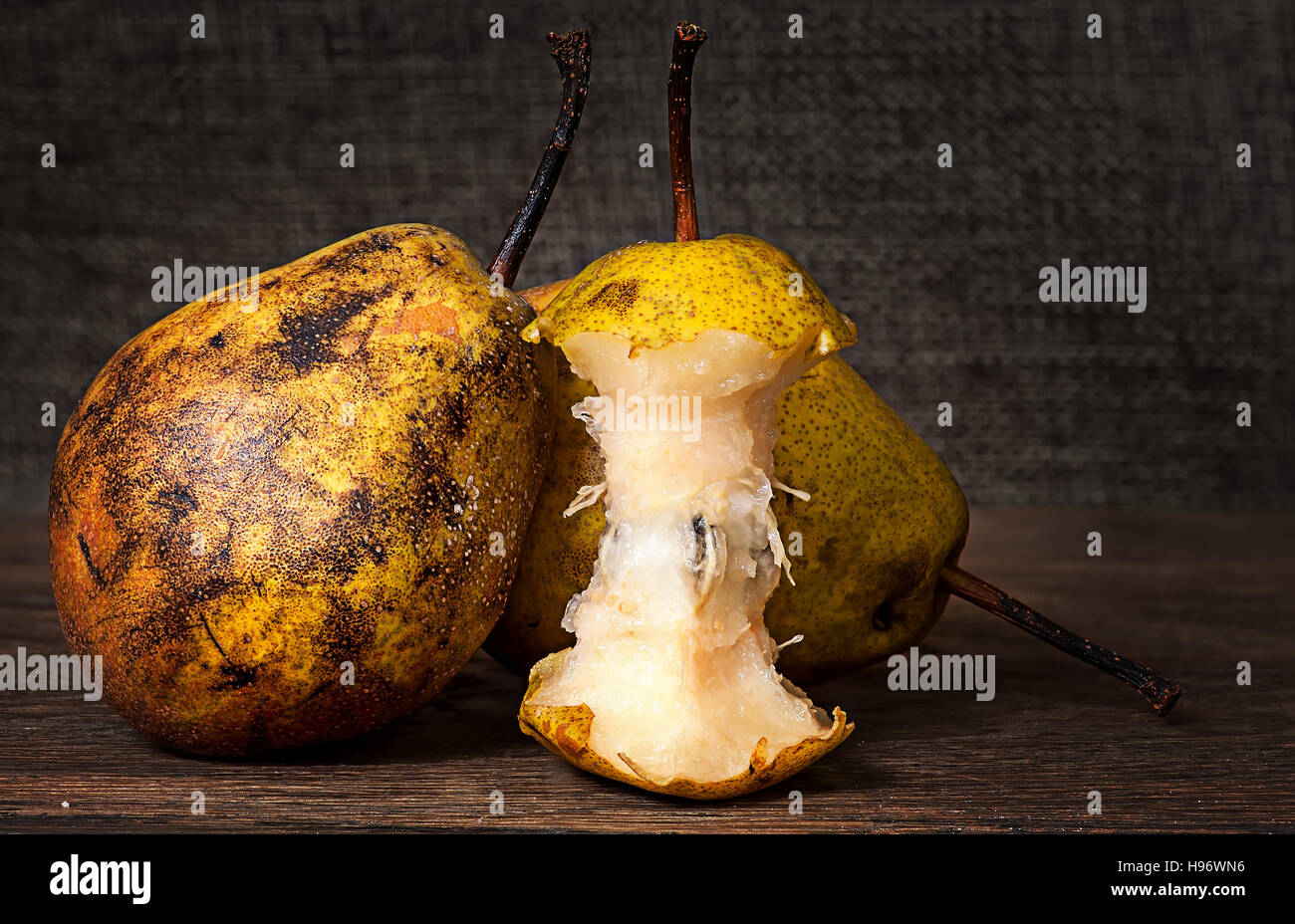 Two pears and stub standing on wooden table background sacking - Stock Image