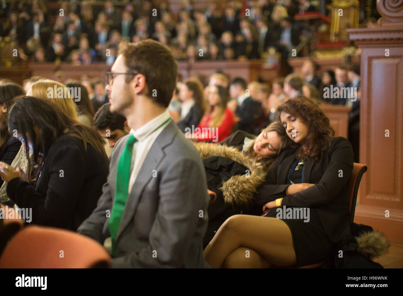 Two students take a nap during the awards ceremony of OxIMUN in the Sheldonian Theatre. From a series of photos - Stock Image