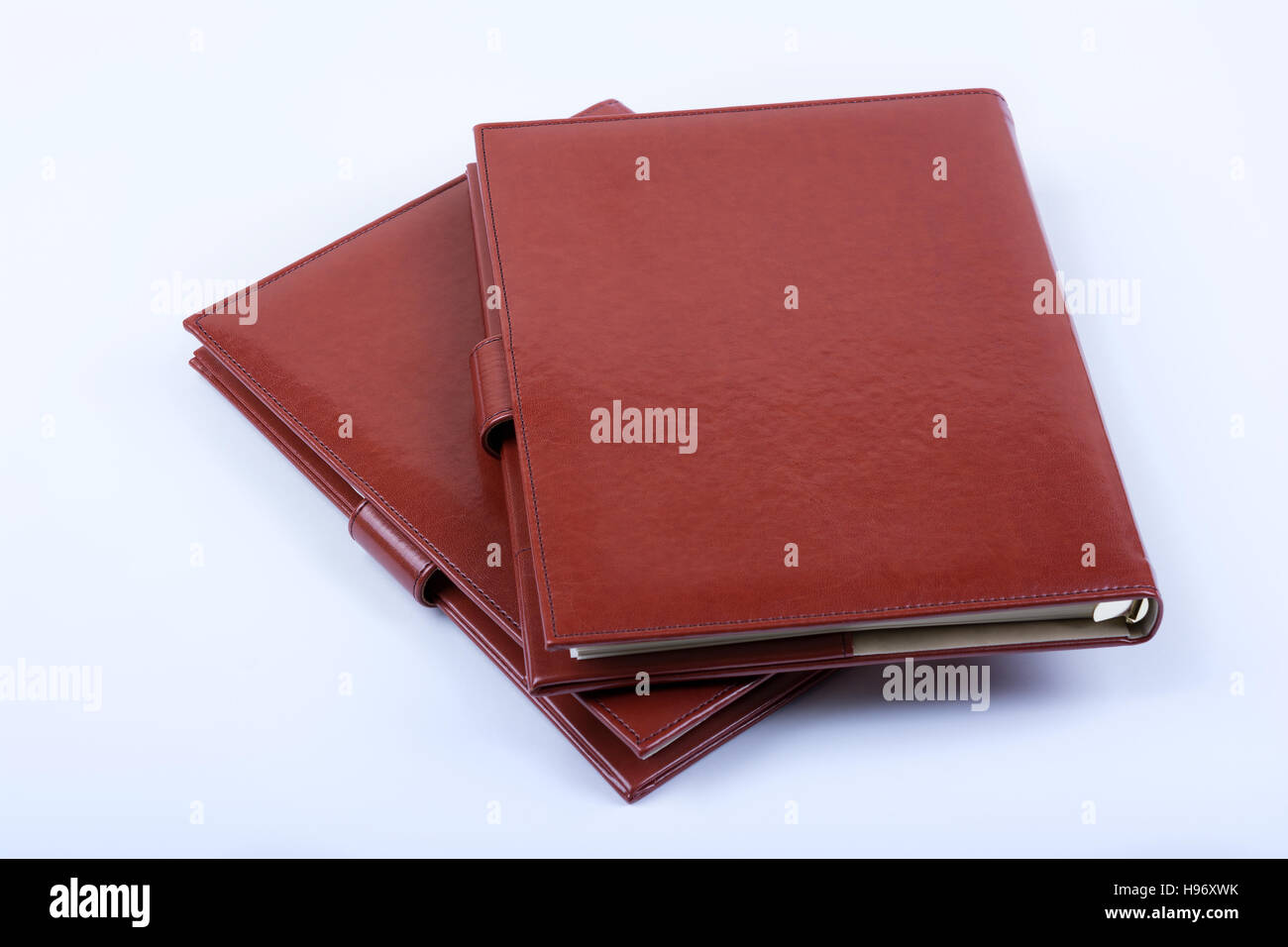 Red leather luxury diaries on white background - Stock Image