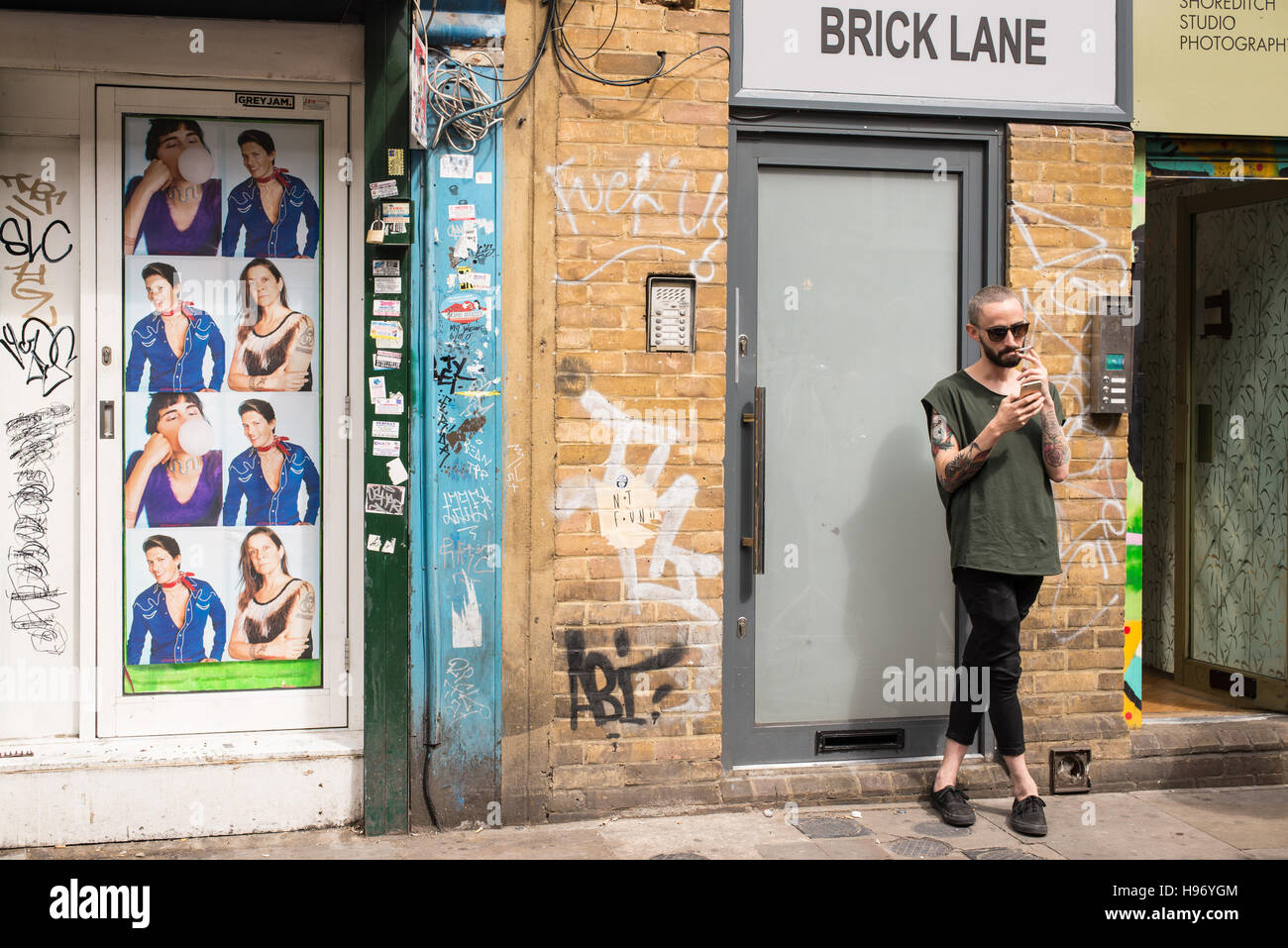 Hipster man with tattooed arms smoking a cigarette in Brick lane, Shoreditch, London, UK. Stock Photo