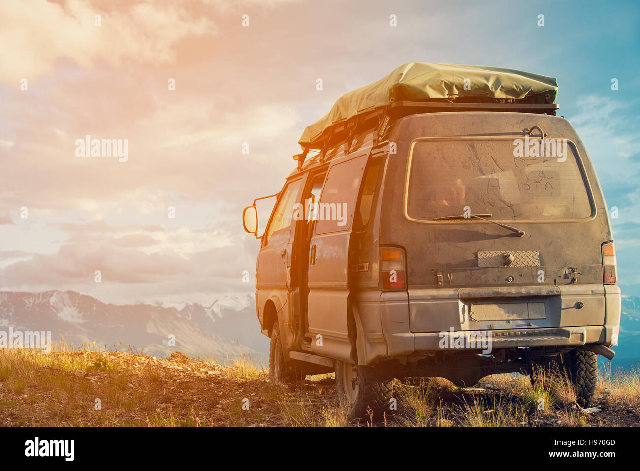Offroad car concept with mountains. Microbus. Post-apocalyptic view. - Stock Image