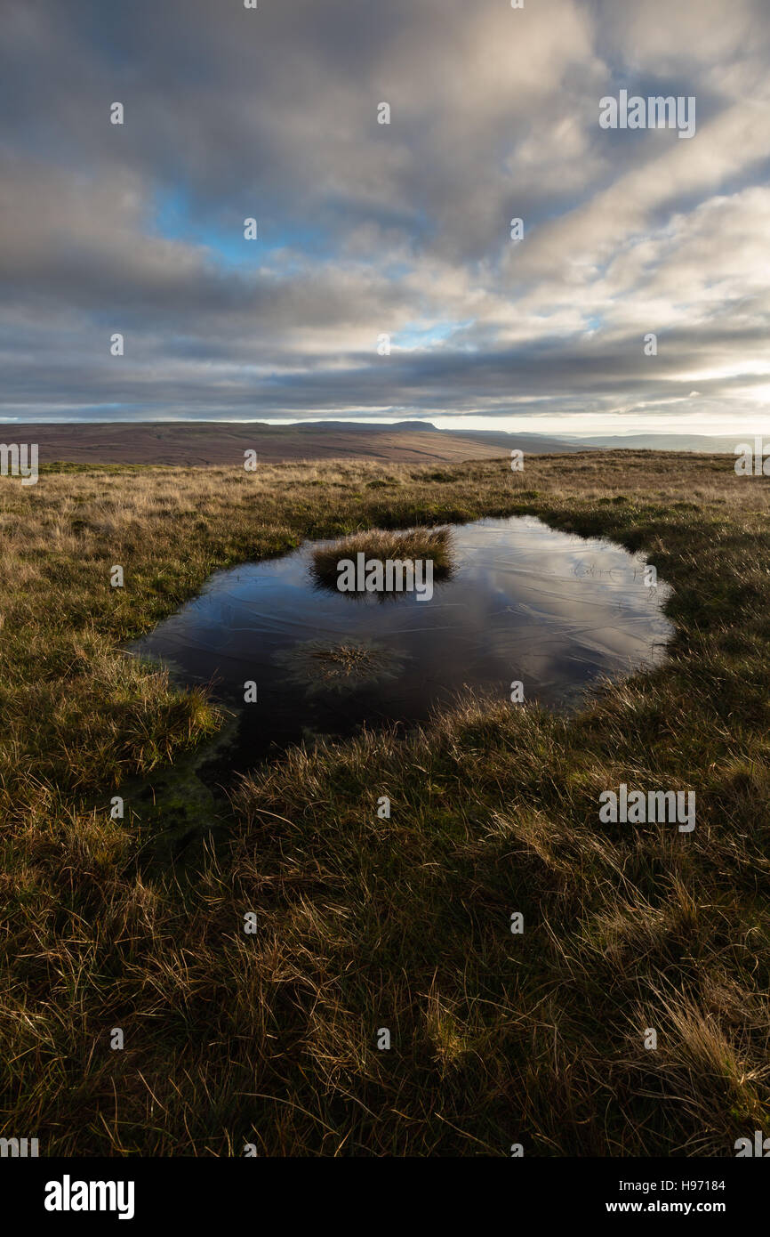Looking over a small frozen tarn on Swineley Cowm across to Pen-y-ghent in the Yorkshire Dales, England, UK - Stock Image