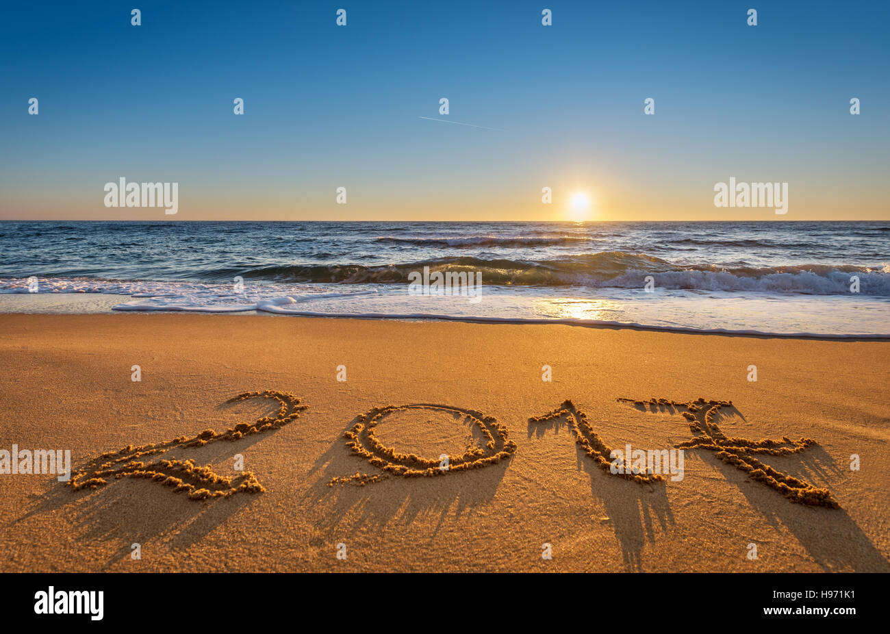 Number 2017 written on seashore sand at sunrise. Concept of upcoming new year and passing of time. - Stock Image