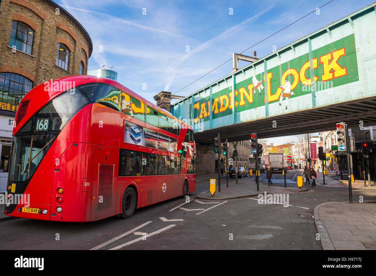 LONDON - NOVEMBER 16, 2016: A red double-decker bus passes under a railway overpass at the popular Camden Lock Market. Stock Photo