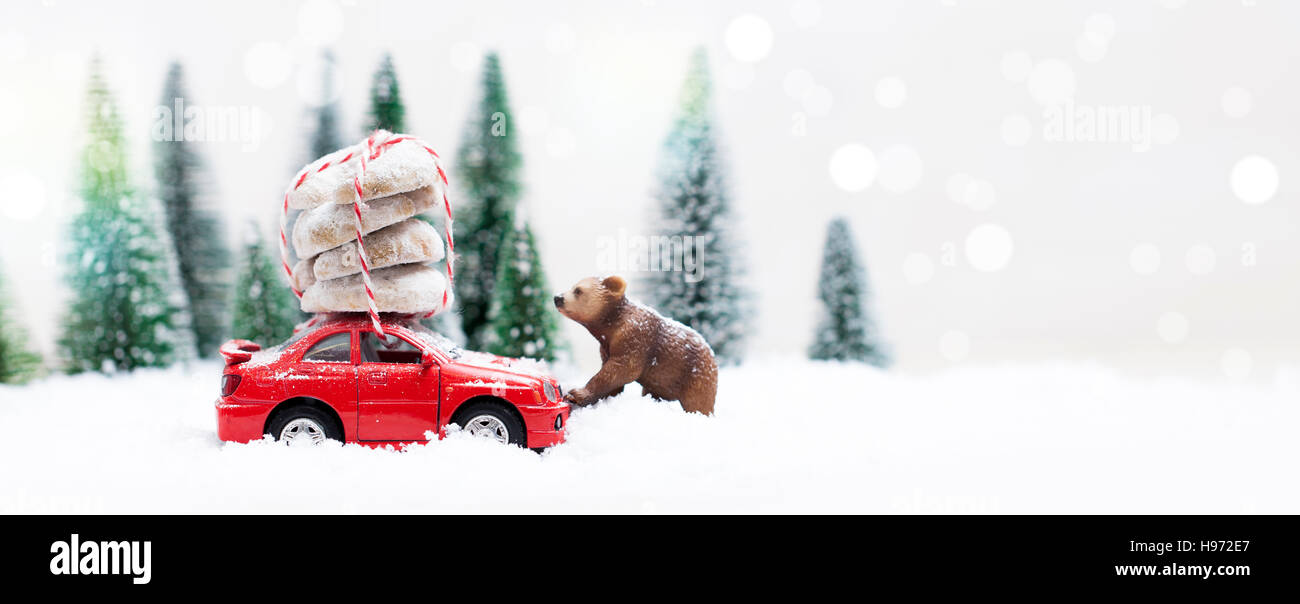 Snowy Winter Forest with a grizzly bear and a miniature red car carrying Christmas Cookies - Stock Image