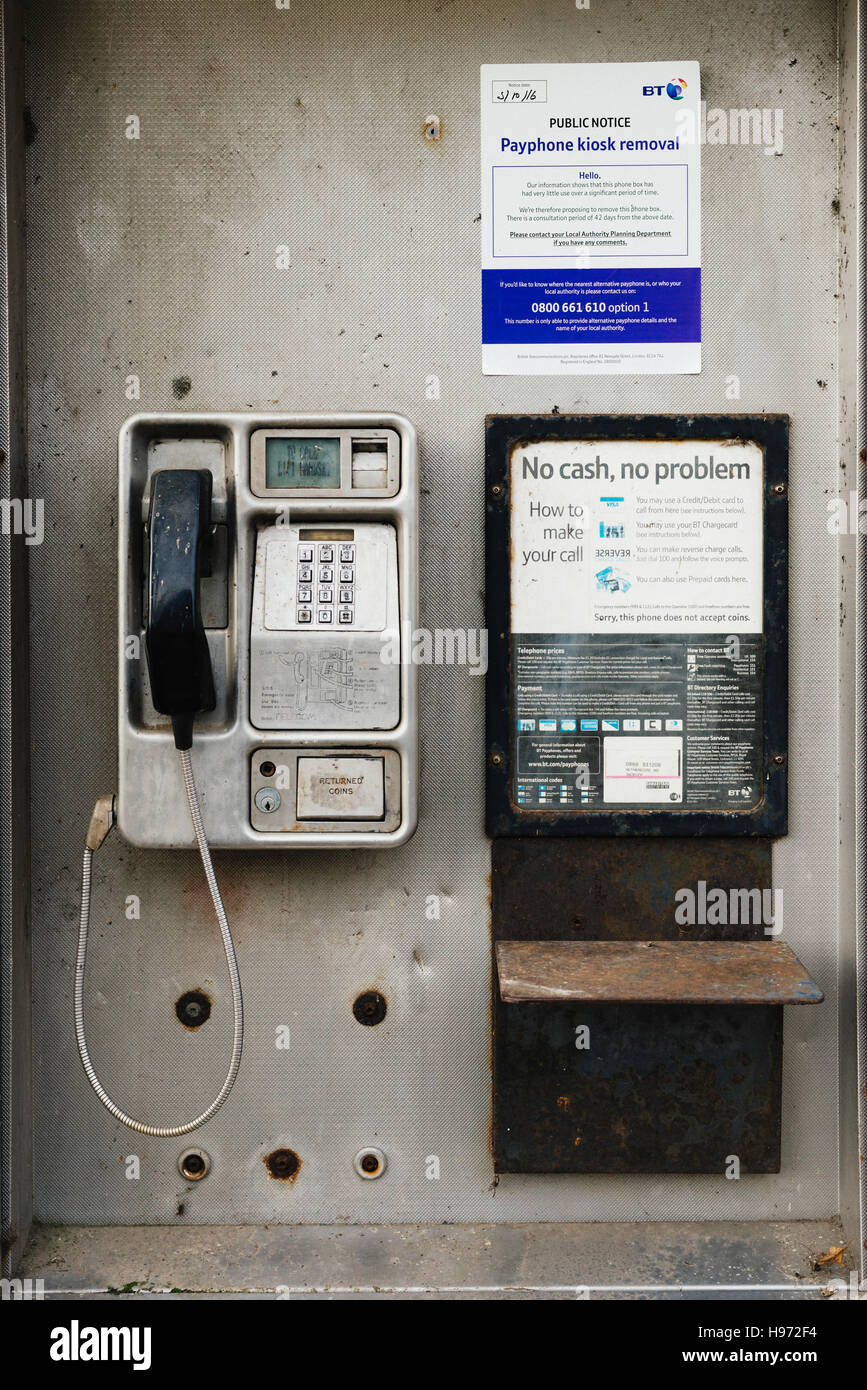 UK public BT payphone in bad condition with notice announcing its imminent removal due to lack of use - Stock Image