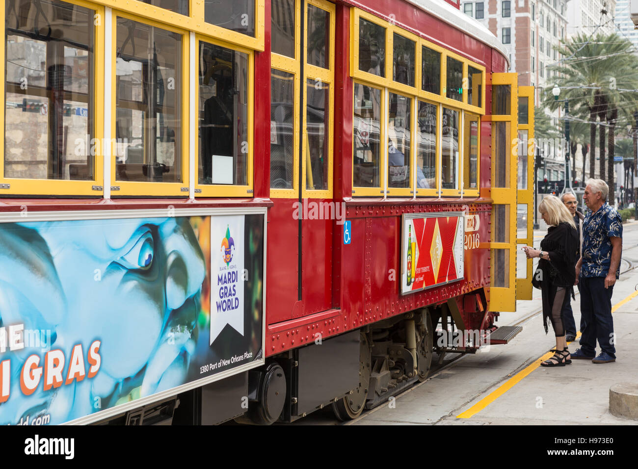 Passengers board an RTA streetcar on Canal Street in New Orleans, Louisiana. - Stock Image
