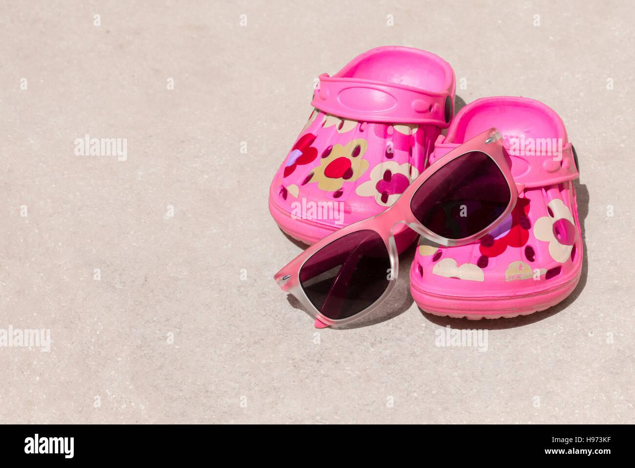 c9609efbf4942 Pink beach kid s crocs and sunglasses on sandy beach.Beach sandals and  sunglasses in the