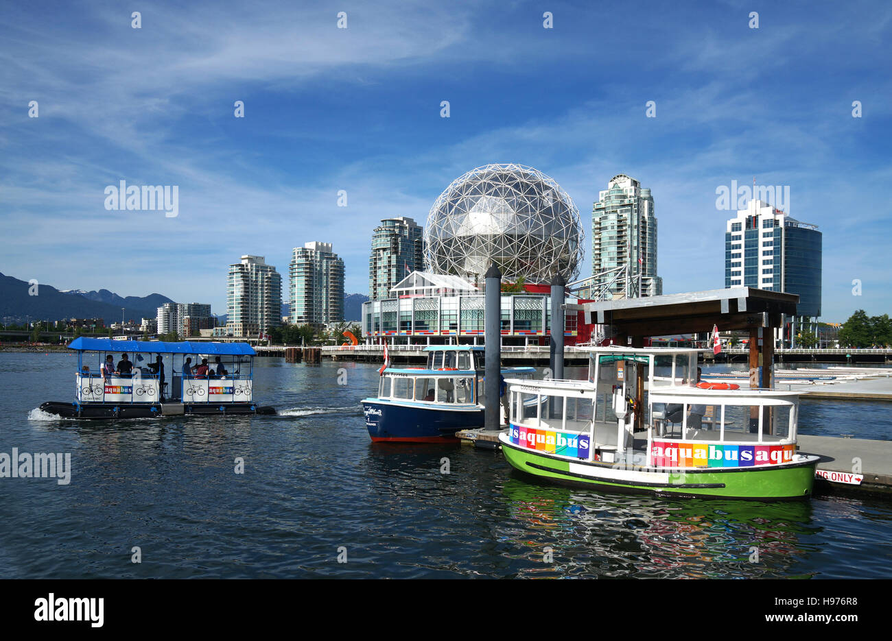 Little ferry boats on False Creek in front of the building of Science World, Vancouver, Canada - Stock Image
