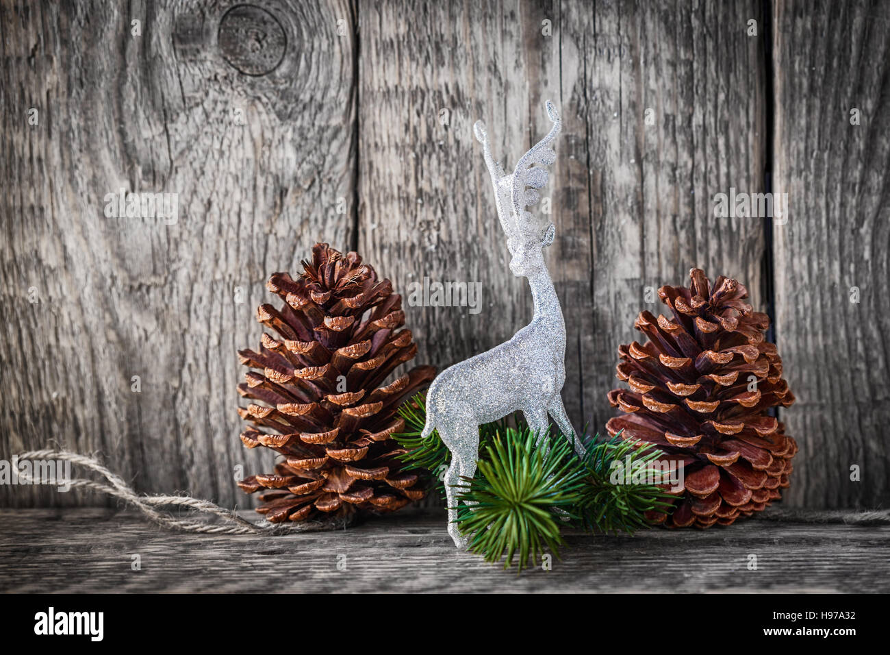 Home decor pine cones  and white deer on a wooden background. - Stock Image