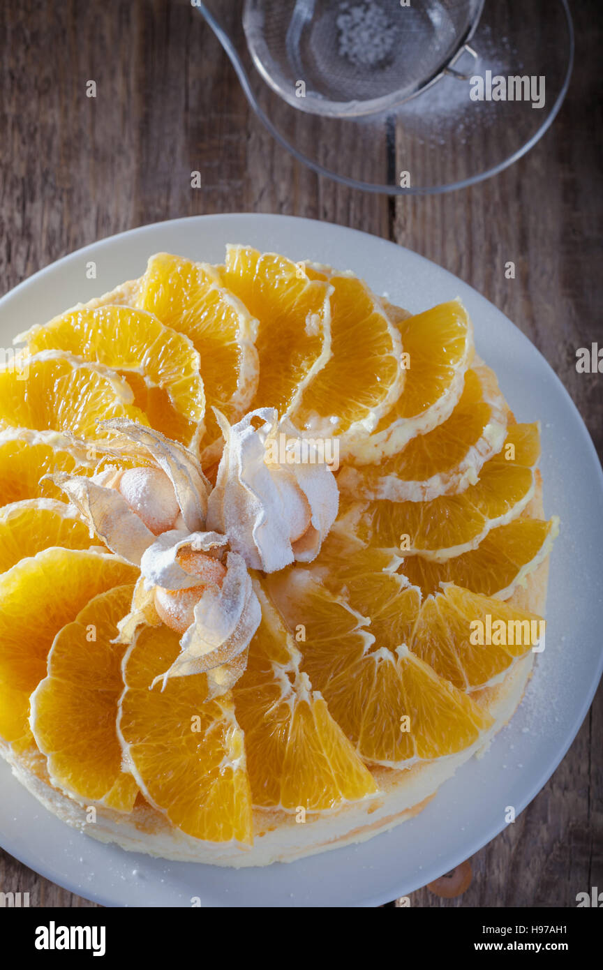 Cheesecake decorated with oranges and physalis on wooden table - Stock Image