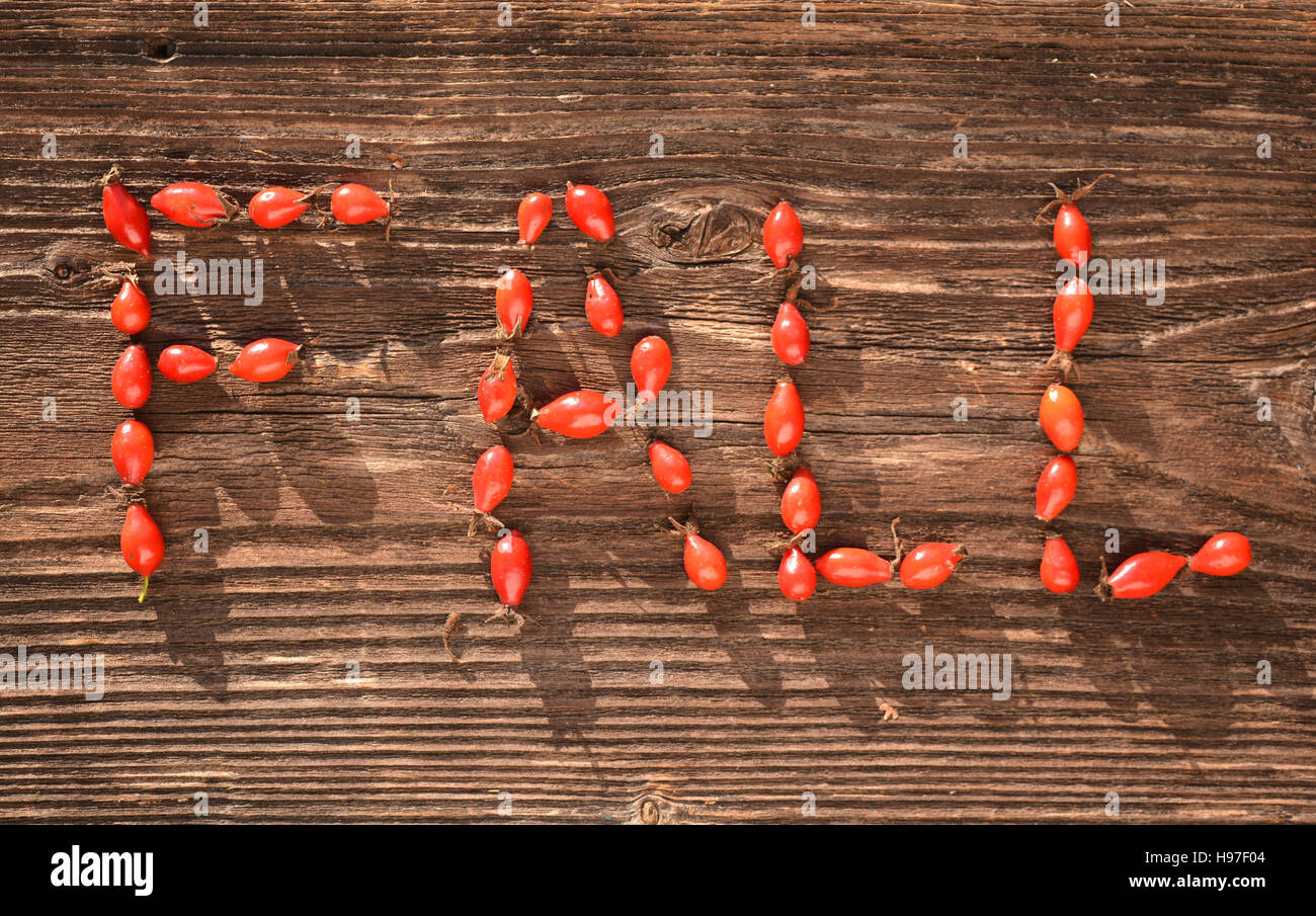 Word FALL made of wild rose hips on wooden table in autumn garden ...